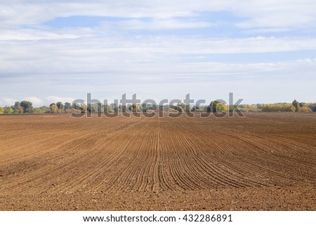 Agricultural field plowed brown soil - stock photo
