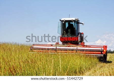 Agricultural image of a large mechanized Swather mowing a grass field to make quality grass hay bales for livestock feed (focus point on Swather).