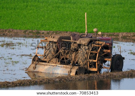 agricultural land being ploughed using an old tractor in modern india - stock photo