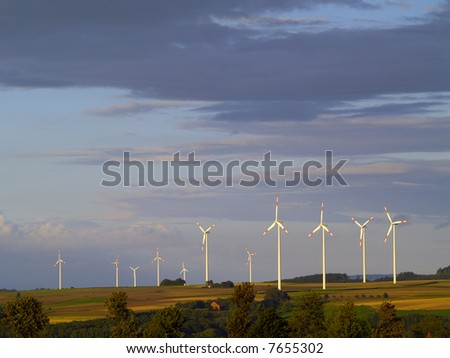 agricultural landscape with wind energy plants in germany, evening light