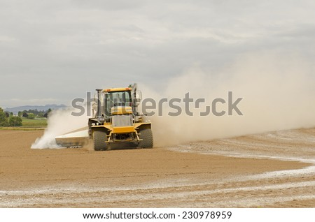Agricultural lime being spread by a big tired truck or tractor  on a newly plowed farm field - stock photo
