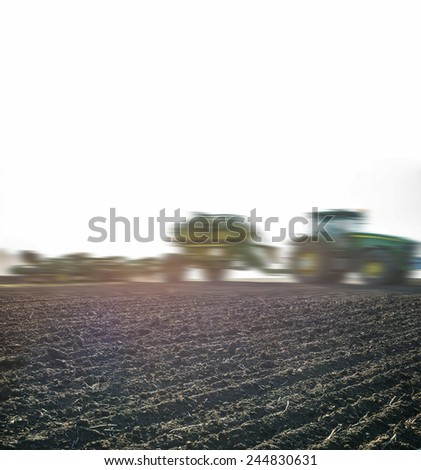 Agricultural machinery mounted Sun light with fug Nature background of empty spring field Land preparation with tractor, agrimotor plows cornfield, agriculture modern method on green grass and forest  - stock photo