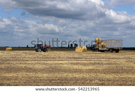 Agricultural machines on the field after harvest under dramatic beautiful autumn sky