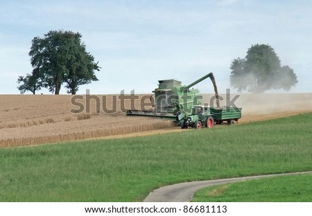 agricultural scenery showing a green harvester at the edge of a crop field while harvesting at summer time in Southern Germany - stock photo