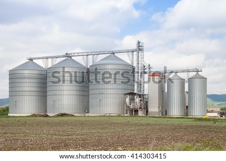 Agricultural Silo - Building Exterior, Storage and drying of grains, wheat, corn, soy, sunflower against blue sky with white clouds