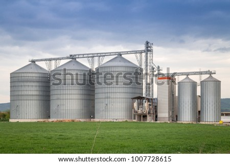 Agricultural Silo, foreground cereals - Building Exterior, Storage and drying of grains, wheat, corn, soy, sunflower against the blue sky with white clouds