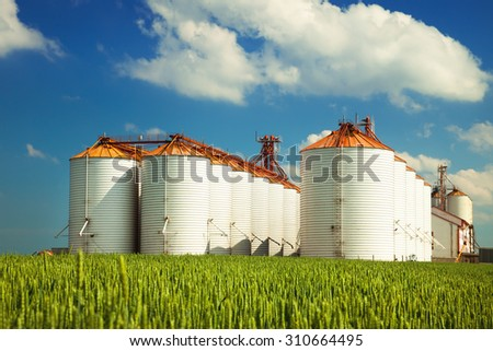 Agricultural silos under blue sky, in the fields - stock photo