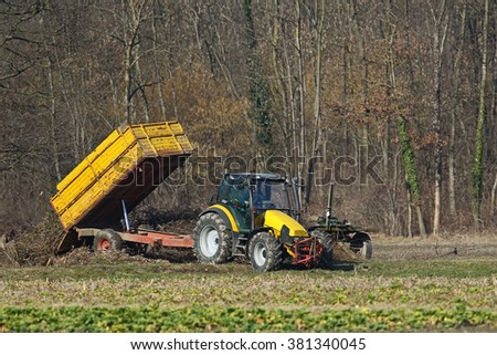 Agricultural tractor at work in a field dumping brush