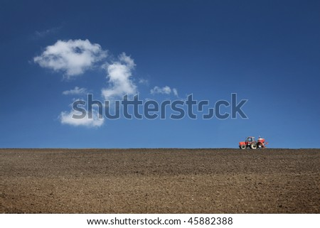 agricultural tractor cultivating on field with blue sky - stock photo