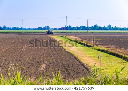 Agricultural tractor intent on fertilization and treatment of a cultivated field in the countryside in Italy - stock photo