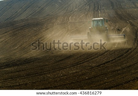 Agricultural tractor working in a plowed field - stock photo