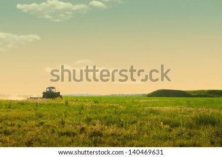 agricultural work in the field at sunset - stock photo