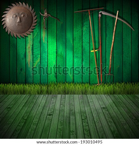 Agriculture Concept Background / Green wooden wall with green grass and wood floor, rake, scythe and pitchfork, pruning shears and a sun wrought iron - Agricultural background concept - stock photo