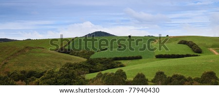 agriculture field green industrial farm land panoramic landscape scenic view across hills - stock photo