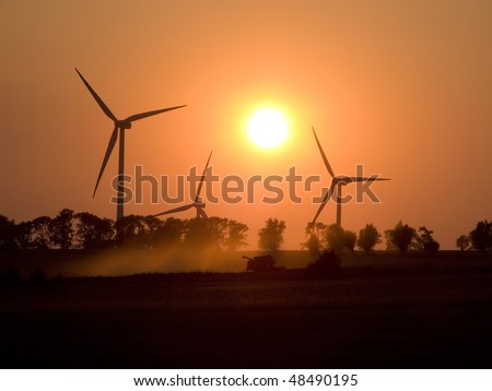 Agriculture. Harvest. Evening mowing of cereal through combine harvester on background of windmills - stock photo