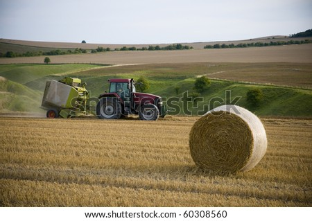 Agriculture landscape with straw bale and a tractor - stock photo