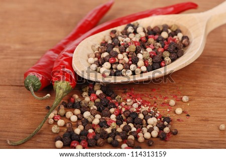 agriculture objects (red hot chilli and some ground peppers) over brown wooden background - stock photo