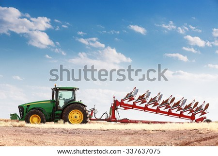 Agriculture plowing farm tractor on wheat cereal field - stock photo