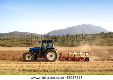 Agriculture plowing tractor on wheat cereal fields working - stock photo