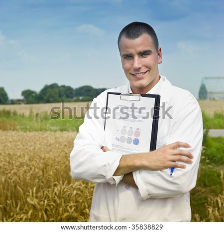 Agriculture scientist making notes in the field with greenhouses in background