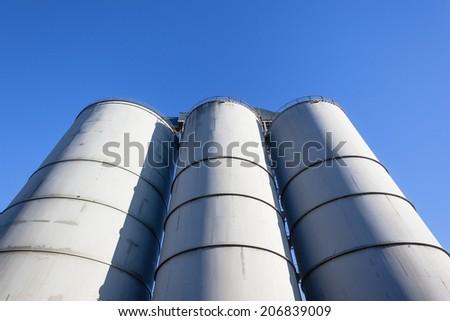 Agriculture Three Grain Silos Blue Agriculture three food storage grain metal silos against blue sky - stock photo