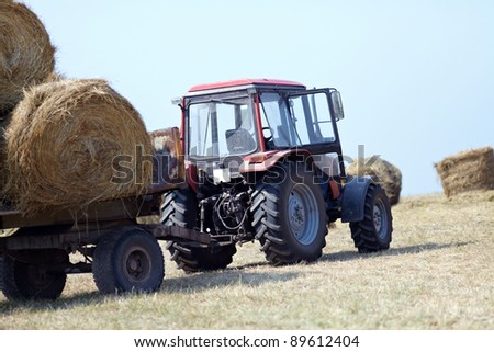 Agriculture - tractor carries a haystack - stock photo