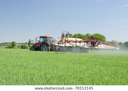 Agriculture - tractor dusting chemical manure (plant protection with pesticides) - stock photo