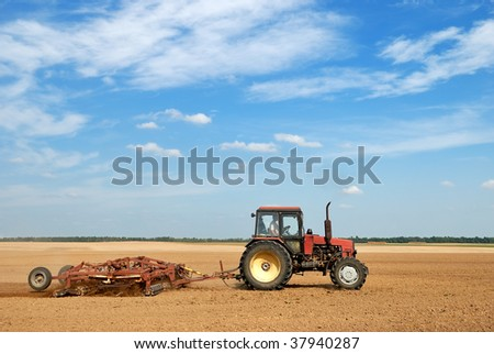 Agriculture tractor in yellow field outdoors in summer with plough - stock photo
