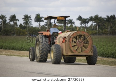 Agriculture tractor towing a blower near a field in Miami Florida - stock photo