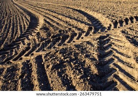 agriculture tractor traces on cultivated farm field soil - stock photo
