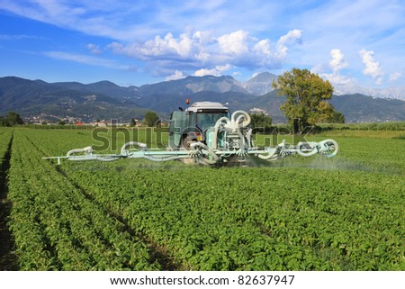 agriculture, tractor with chemical treatment spraying pesticide on cultivated field - stock photo