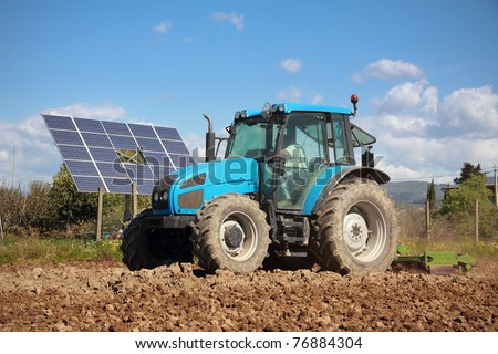 agriculture, tractor working on a field with photovoltaic solar panel in background - stock photo