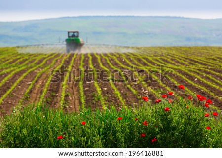 Agriculture with old tractor in a green field with blue background