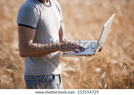 Agronomist analysing wheat market using laptop - stock photo