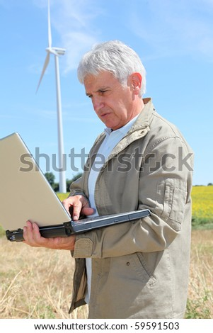 Agronomist in wheat field with laptop computer - stock photo