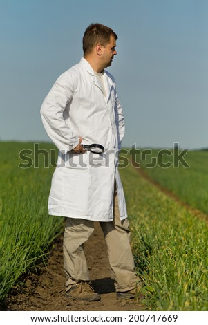 Agronomist in white coat with magnifier in hand standing in onion field - stock photo