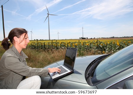Agronomist with computer in field with wind turbines - stock photo