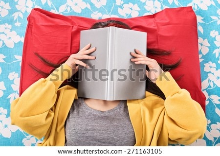 Ah, this read never seems to end. Young girl in her bed covering her face with an open book, as if she's really tired/bored of reading - stock photo