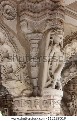 AHMEDABAD, GUJARAT, INDIA - AUGUST 21 : Hutheesing Jain Temple on August 21, 2012 in Ahmedabad. Sculpture of a dancing girl  ( Apsara ) on an ornated column decorated with beautiful stone carved arch. - stock photo