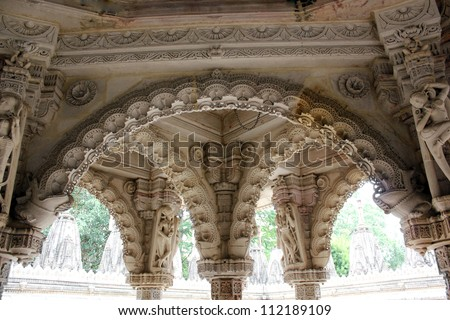AHMEDABAD, GUJARAT, INDIA - AUGUST 21 : Hutheesing Jain Temple on August 21, 2012 in Ahmedabad. Ornated stone carved arches on the colonnaded columns of ' Rangamandapa ' hall for musical performances. - stock photo