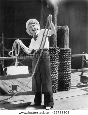 Ahoy, from a young woman in a sailor's outfit, holding a heavy rope - stock photo