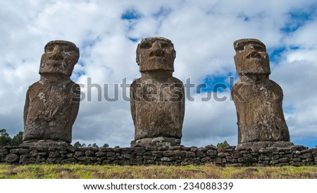 Ahu Akivi: Moai (statues) number 2, 3 and 4 from left to right with a cloudy sky behind. Rapa Nui / Easter Island / Isla de Pascua, Polynesia, Chile. - stock photo