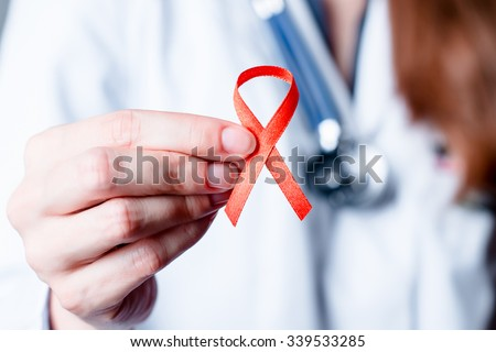 AID, HIV red ribbon. Symbol of awareness, charity, support in disease, illness, ill. Medical health care, help and hope. Sign of healthcare medicine campaign holding in female doctor hand.   - stock photo