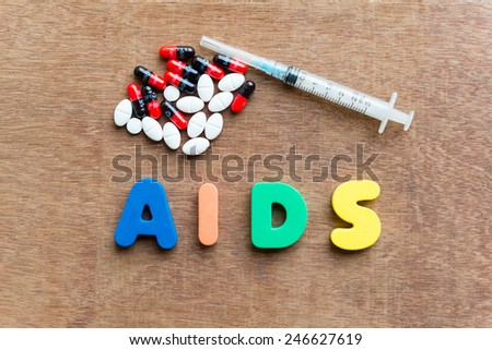 aids colorful word in the wooden background - stock photo