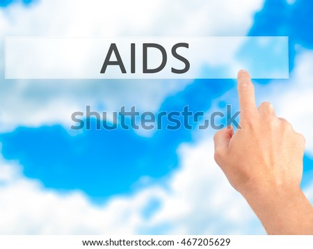 AIDS - Hand pressing a button on blurred background concept . Business, technology, internet concept. Stock Photo