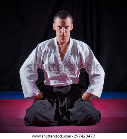 Aikido fighter on black background - stock photo