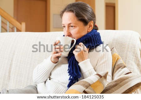 Ailing middle-aged woman sitting on  couch with  cup of tea - stock photo