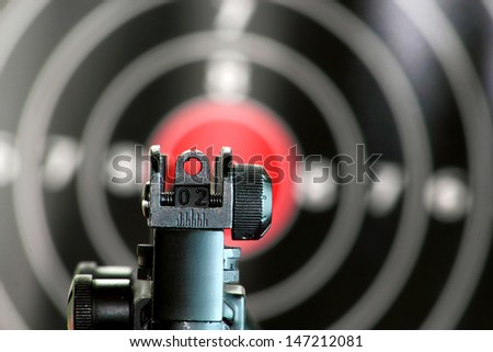 Aim sight of a gun pointing to the center of the target - stock photo