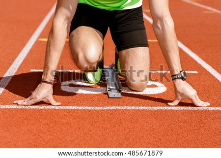 Aiming for victory. Low section cropped shot of a runner at the starting position ready to start the race at the stadium