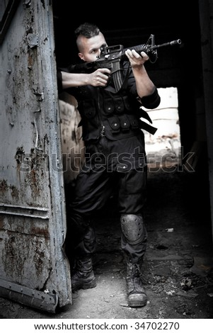 Aiming man with M4 rifle on the ruined building background. - stock photo